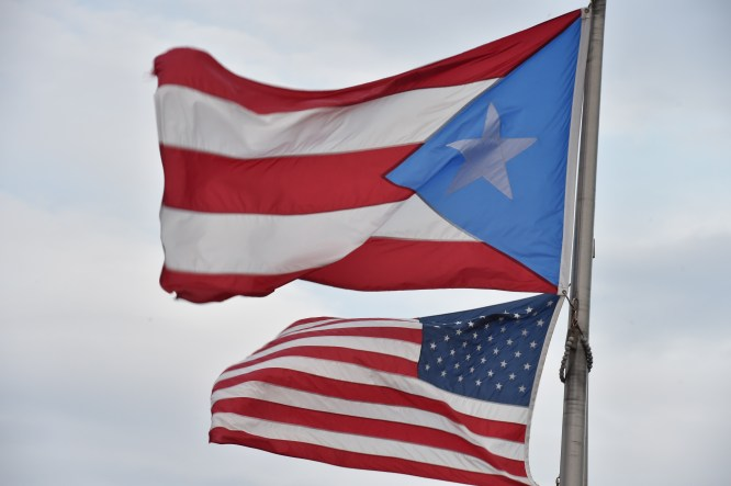 (FILES) This February 9, 2015 file photo shows the Puerto Rican and US flags in the Old Town district in San Juan, Puerto Rico.  The US Treasury Department on October 21, 2015 proposed a plan to rescue Puerto Rico from default, but said that it needed approval from the Republican-controlled Congress.The finances of the Caribbean island -- a US territory since the 1898 Spanish-American War -- were dealt a crippling blow in 2006 with the loss of federal tax breaks for US companies with local operations. AFP PHOTO/PAUL  J. RICHARDS